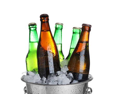 Birra nel secchio di metallo con ghiaccio isolato su bianco