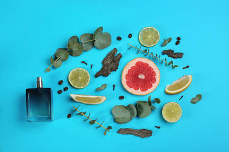 Beautiful flat lay composition with bottle of perfume, eucalyptus, tree bark and citrus fruits on blue background