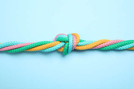Colorful ropes tied together on light blue background, top view. Unity concept