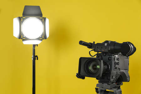 Professional video camera and lighting equipment on yellow background