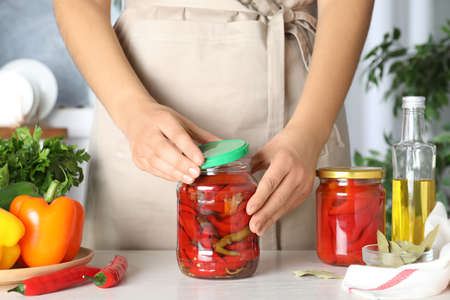 Woman closing jar with pickled peppers at white table, closeup Stock Photo