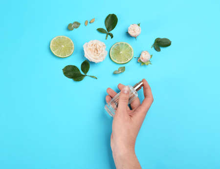 Top view of woman spraying perfume on blue background, flowers and lime representing aroma