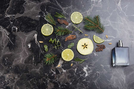 Flat lay composition with bottle of perfume on black marble background
