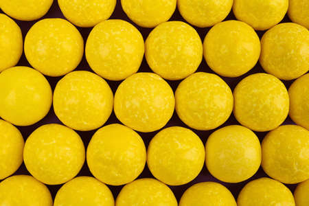 Delicious lemon chewing gums as background, top view