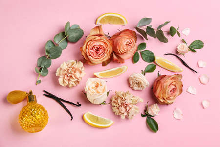 Beautiful flat lay composition with bottle of perfume, lemon and flowers on pink background