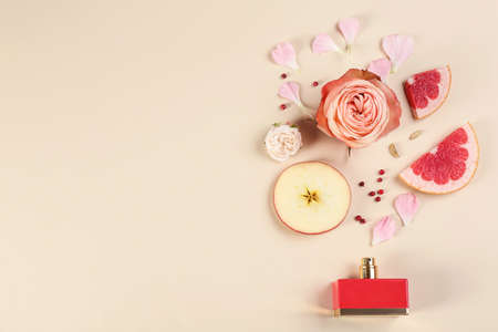 Flat lay composition with bottle of perfume on beige background, space for text