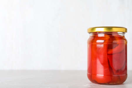 Glass jar of pickled red bell peppers on light marble table. Space for text