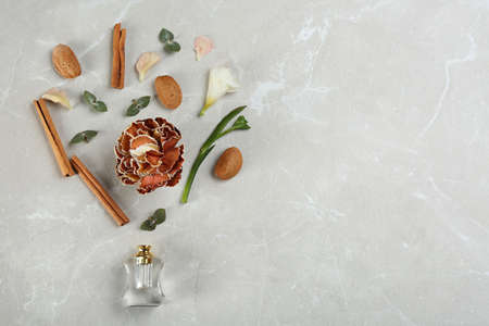 Flat lay composition with bottle of perfume on marble background, space for text