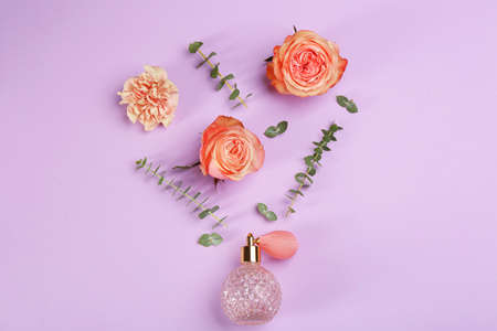 Beautiful flat lay composition with bottle of perfume, eucalyptus and flowers on lilac background
