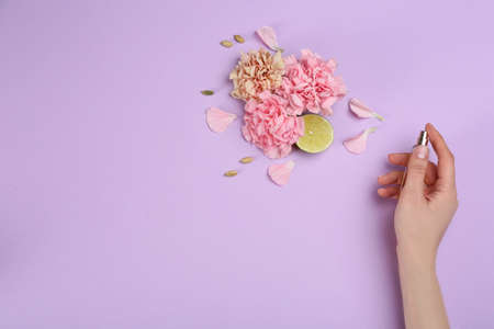 Top view of woman spraying perfume on lilac background, flowers and lime representing aroma. Space for text