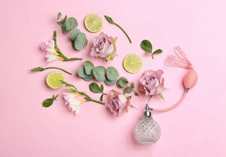 Beautiful flat lay composition with bottle of perfume, lime, eucalyptus and flowers on pink background Stock Photo