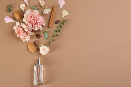 Flat lay composition with bottle of perfume on light brown background, space for text