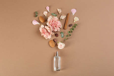 Flat lay composition with bottle of perfume on light brown background