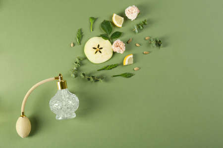 Flat lay composition with bottle of perfume on green background, space for text