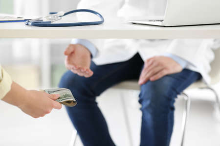 Patient giving bribe to doctor under table in clinic, closeup. Corrupted medicine Archivio Fotografico