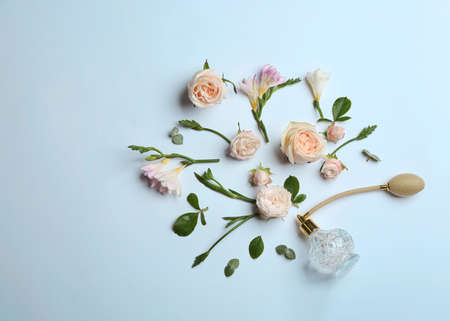 Beautiful composition with bottle of perfume and flowers on white background, flat lay. Space for text