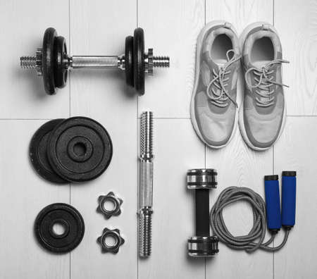 Gym equipment and shoes on wooden floor, flat lay