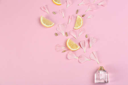 Flat lay composition with bottle of perfume on pink background, space for text