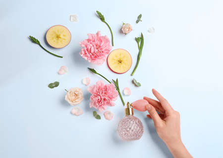 Top view of woman spraying perfume on white background, apple and flowers representing aroma Stock Photo