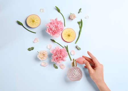 Vista superior de la mujer rociando perfume sobre fondo blanco, manzana y flores que representan el aroma Foto de archivo
