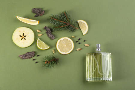 Flat lay composition with bottle of perfume on green background
