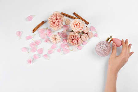 Woman with perfume. Fragrance composition, flowers and cinnamon on white background, top view