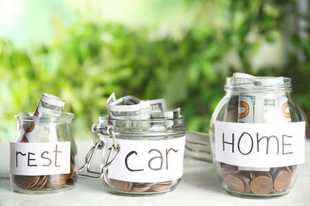 Glass jars with money and tags REST, CAR, HOME on white table against blurred background