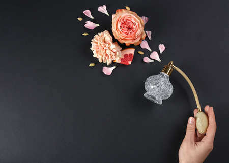 Woman with perfume. Fragrance composition, flowers and grapefruit on black background,  top view. Space for text