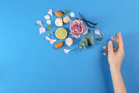 Frau mit Parfüm. Duftkomposition, Blumen und Limette auf blauem Hintergrund, Ansicht von oben