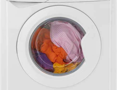 Modern washing machine with laundry isolated on white, closeup