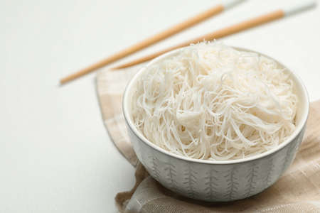 Tasty cooked rice noodles on white table