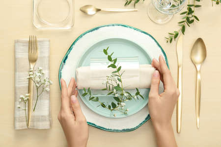 Woman setting table with green leaves for festive dinner, top view