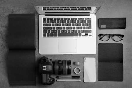 Flat lay composition with laptop, camera and smartphone on grey stone table. Designer's workplace