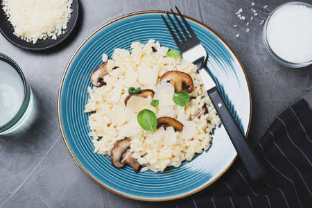 Delicious risotto with cheese and mushrooms on dark grey table, flat lay Imagens