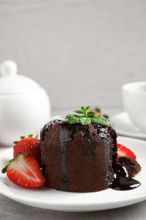 Delicioso pastel de lava de chocolate caliente con menta y fresas en la mesa. Espacio para texto