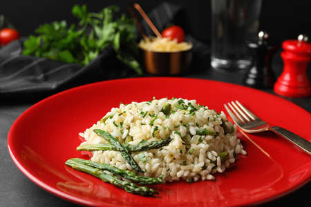 Delicious risotto with asparagus in plate, closeup