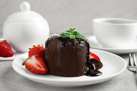Delicious warm chocolate lava cake with mint and strawberries on table