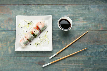 Delicious rolls wrapped in rice paper on light blue wooden table, flat lay