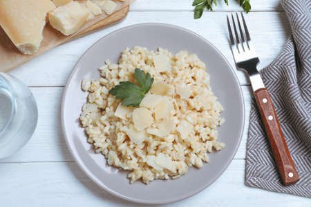 Delicious risotto with cheese on white wooden table, flat lay Imagens