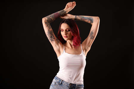 Beautiful woman with tattoos on arms against black background