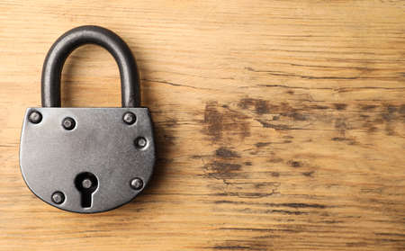Steel padlock and space for text on wooden background, top view. Safety concept
