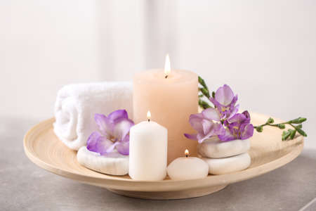 Beautiful composition with spa stones and burning candles on grey table Stock Photo