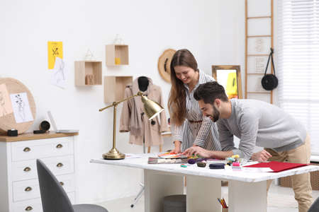 Fashion designers creating new clothes in studio