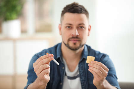 Man with nicotine patch and cigarette at home, focus on hands 스톡 콘텐츠