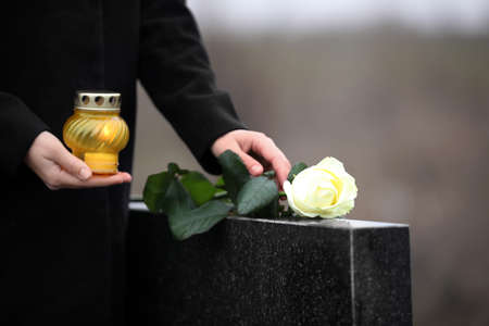 Woman with candle and rose near black granite tombstone outdoors, closeup. Funeral ceremony