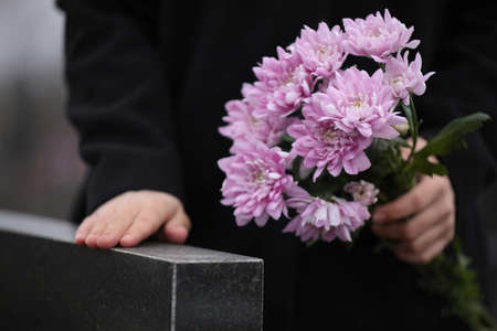 Woman holding chrysanthemum flowers near black granite tombstone outdoors, closeup. Funeral ceremony