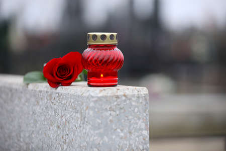 Red rose and candle on light grey granite tombstone outdoors. Funeral ceremony 스톡 콘텐츠