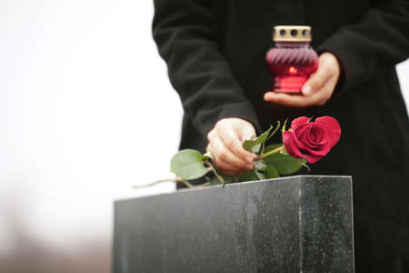 Woman with candle near black granite tombstone outdoors, focus on red rose. Funeral ceremony