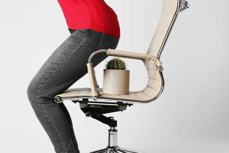 Frau sitzt auf Stuhl mit Kaktus vor weißem Hintergrund, Nahaufnahme. Hämorrhoiden-Konzept
