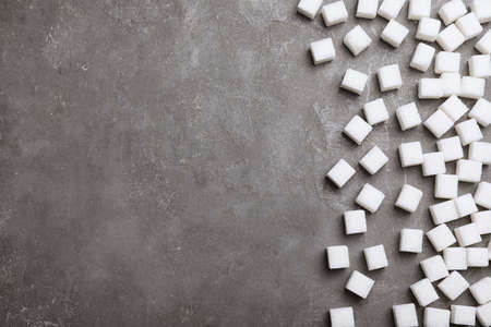 Refined sugar cubes on grey table, top view. Space for text